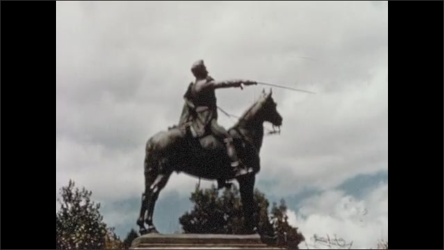 1950s: Aerial view of dense city. Statue of man on horse with sabre.