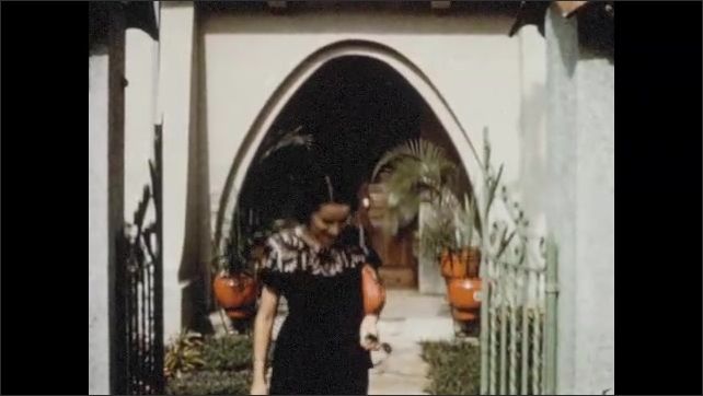 1950s: Woman and girl walk from apartment building. Woman walks from traditional villa home. Children play on grass in park. Woman and children walk through covered garden.